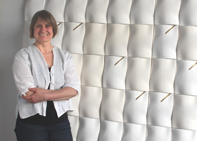 Regina Heinz in front of one of her ceramic feature walls.